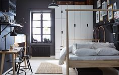 A dark grey and white bedroom that's shared by a parent and child with an adult's bed, child's loft bed, wardrobes and a desk
