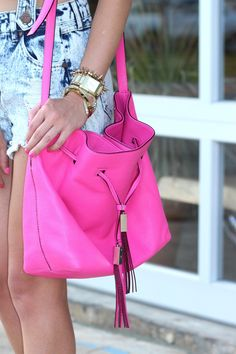 Bracelet layers and a neon pink bucket bag with tassels by Kate Spade