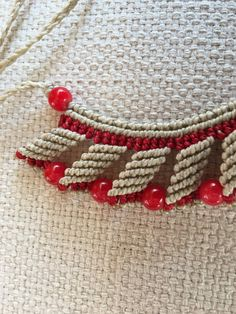 Collar en macramé hecho a mano con hilo encerado en color beige y rojo con cuentas haciendo juego en rojo. Cierre ajustable con nudo corredizo