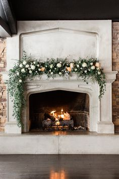 A gorgeous cascading fireplace mantel floral arrangement with mixed greenery including Italian ruscus and eucalyptus and white blooms of roses and lisianthus. Photo: Stephanie Couture Photography Venue: The Lake House Calgary spring wedding Wedding Fireplace Decorations, Wedding Mantle, Aisle Decorations, Decor Wedding, Wedding Ideas, Garden Deco, Wedding Flower Arrangements, Floral Arrangements, Wedding Centerpieces