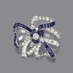 SAPPHIRE AND DIAMOND BROOCH, OSCAR HEYMAN BROTHERS INC., CIRCA 1950 Designed as a bow and floral spray, set in the center with a round diamond weighing approximately .50 carat, completed by 6 marquise-shaped, 34 round and 19 baguette diamonds weighing approximately 5.50 carats, further decorated with 3 oval-shaped and 25 square-cut sapphires, mounted in platinum, signed OHB and numbered 69908.
