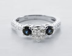 V Carved Ring || Heart Shaped Diamond Three Stone Ring With Blue Sapphire In 18k White Gold