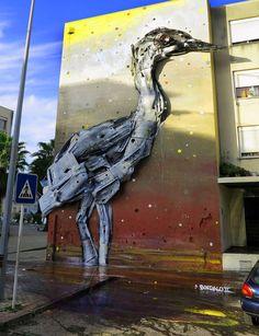 Лиссабон на основе уличный художник Бордалло II ( ранее ) недавно завершил работу над двумя новыми установками птиц, совы и цапли, созданных из окрашенного мусора и других предметов, прикрепленных к стене.