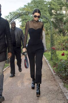 Kendall Jenner just cut your Fri-yay night getting-ready time in half with the sleekest all-black everything ensemble. Refresh a sheer-panel jumpsuit with patent platform ankle boots and you're more than set