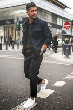 Kosta Williams crosses the street in a H&M black shirt and Puma sneakers