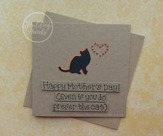 Unique funny Mothers Day card with a cat silhouette and gem heart for Mum / Mom. This handmade cat card for Mum (or Mom) has a silhouette of a cat sitting happily with gems in the shape of a heart. The colour of the shadow of the cat and the gems can be selected from the drop-down menu. The sentiment on this Mothering Sunday cat card is added with 3D foam and reads: Happy Mothers Day (even if you do prefer the cat) PERSONALISING YOUR CARD: You can choose the colour of the matching shad...
