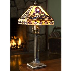 """Stained Glass Trinity Knot Lamp.    The rich colors in this glass lamp make it a focal point in any room. The shade rests solidly on a heavy metal base. Imported. 18"""" tall."""