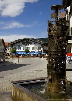 -Fountain and painted facade of Restaurant Alte Post in Oberammergau, Bavaria, Germany