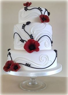 """POPPY WEDDING CAKE : 3 Tier Poppy Wedding Cake with a hint of Baroque in the white swirls and  black Poppy stem accents.  (Although this cake is classed as a 3 tier it is actually 4 tiers, as the middle is double in depth)    Top Tier 6""""  Middle Tier 8"""" (double depth)  Bottom Tier 10""""     £480       Serves approx 120    (Brandy soaked fruit cake at extra cost)"""