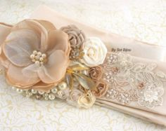 ***Made Upon Request  This romantic and feminine bridal sash, like my other creations, is filled with detail. This piece is an exquisite combination of textures. Blush pink and ivory combine to perfection in this one-of-a-kind piece. The focal flower is a handmade multi-petal bloom made with blush chiffon and embellished with a sparkly crystal jewel. The rest of the flowers are a combination of satin and chiffon in complementary shades. Quality crystal and pearl jewels, as well as my…