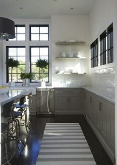 gray cabinets & floating shelves | glossy white subway tile | steel casement windows