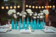I collected bottles all year long with help from lots of friends! Painted bottles and used flowers from Sam's Club. Inexpensive and DIY. Brett Jarnagin - Destin, FL Wedding