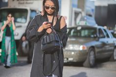 A tank top, black jacket, skinny scarf are worn with a white skirt, black satchel, and tortoiseshell sunglasses