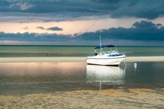 Boat on Cape Cod Bay sits quietly ahead of a storm at sunset