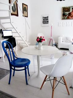 White tile floor and white open staircase. love the blue chair that stands out. M & A dekor