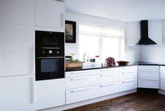 Moderne, hvitt kjøkken i stram stil. Det mørke tregulvet er en fin kontrast til alt det lyse.