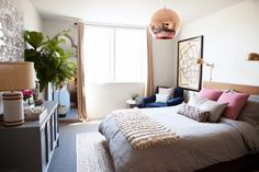 Chic bedroom with eye-catching copper pendant, pink tones, and rich textiles