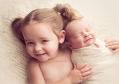 newborn cuddles with sibling