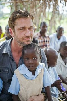 12/20/13 Gerard Butler plays with children in Liberia while helping Mary's Meals My heart just melted all over the place