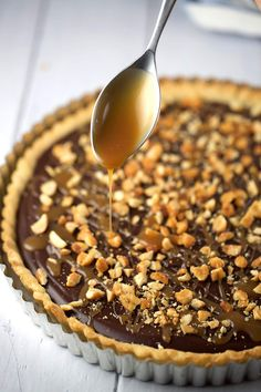 Spoon drizzling caramel over chocolate tart