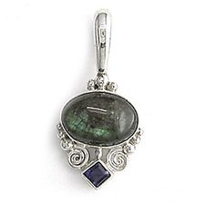 """Lovely petite pendant with a 15x10mm cabochon oval of labradorite and a 3mm kite of Iolite. Hand set sterling silver swirls and beads surround. The blue-green chatoyance of labradorite makes this a much sought after stone. 1/2"""" bail"""