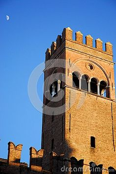 Photo made at the palace of King Enzo of Sardinia, which is located in the city of Bologna in Emilia Romagna (Italy). In the picture you see the upper part of the great crenellated tower with a square plan sunlit next alll sunset. To the left of the tower in the blue sky we see half of the evening moon index that is coming.