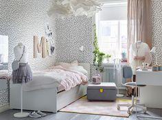 Chambre d'enfant avec murs blancs constellés de taches noires et lit blanc avec linge de lit rose pâle.