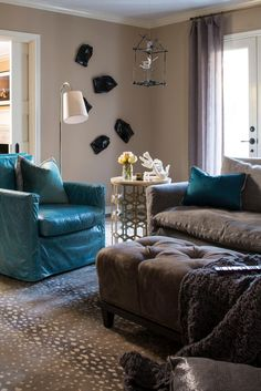 An armchair with aqua-colored leather upholstery adds a major punch of color to the corner of this family room. Taupe walls and furnishings in shades of brown and gray ensure the space feels warm and comfortable.