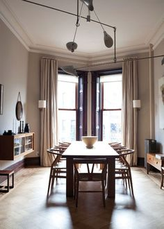 dining room with interesting angled windows and Wishbone chairs by Hans J. Wegner in a Brownstone in Brooklyn