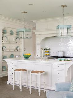 Designer Louise Brooks spices up her white kitchen with accents of palest aqua on light fixtures, small dot tiles in the range backsplash, and decorative plates in a floor-to-ceiling plate rack. Kitchen Trends for 2013 - Traditional Home®