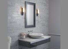 This Contemporary Bathroom Features A Vanity And Floating Sink. The Gray  Brick Walls Are Adorned With Light Sconces. A White Armchair Accents The  Space.