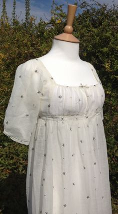 c1805-10 white muslin dress with star and dot design in metallic thread. Short puff sleeves. Back fastening with ties.