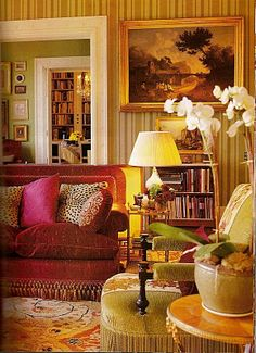 Velvet couch and chair, striped walls, orchids, painting, antiques - bright pillows - Jeffrey Bilhuber
