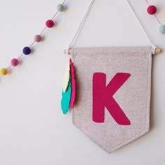 These mini banners feature a single bold letter and group of three feathers - all in your choice of colours.   These would be perfect on bedroom doors, play rooms or any wall that needs a pop of colour.  Made from a beautiful light linen and bright woolen felt letters, these gorgeous, bright banners instantly add colour and character to walls.  Perfect for big and little people alike.  These banners measure 21cm wide and 28cm tall, with a rope and wooden dowel for hanging.  This ...