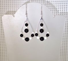 Pretty Mystic Black and Ivory (gem) Swarovski Pearls on silver teardrop hoops. Available in all Swarovski pearl colors - if you need to see photos of colors, convo me. Comes in a lovely gift box. Available on French wires, leverbacks or posts.