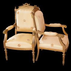 Lot #6: Pair of Gilt Wood Arm Chairs  DESCRIPTION:Pair of superb gilded wooden arm chairs with floral elements throughout the chairs. Topped with a crossed quiver of arrows and torch pediment. Finished with golden upholstery featuring am array of stars along the back and arms of the chair.  CIRCA:20th Ct. ORIGIN:France DIMENSIONS:H:41″ L:24″ W:22″