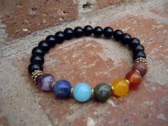 A meaningful wrist mala representing the seven chakras. The stones used are onyx, red jasper, carnelian, citrine, green jade, amazonite, lapis lazuli,