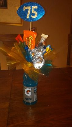 """Wolverine Football Gatorade Candy Favors...Blue Gatorade Bottles, 2 inch Styrofoam balls hot glues to the top, candies taped or hot glues to wooden sticks (skewers)...cellophane and foil squares (approx 6"""" x 6"""") pinched and secured by craft push pins...added players number to hand cut footballs and secured on skewer...KIDS LOVED these!"""