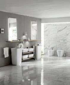 Composition distinguished by KI Cristalplant® floorstanding monobloc washbasins with their strong visual impact. The two slanted mirrors and the large shelf in Hono Elm Decorative Melamine emphasise the strikingly simple and contemporary styling of the room.