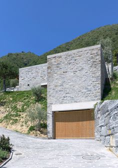 Garage.....swimming pool concealed in stone block over door.   Brione House / Wespi de Meuron