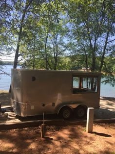 7×16 Cargo Craft Cargo Trailer converted into cozy tiny home on wheels. Has a queen size bed, fold out table, tons of storage under the bed, Has hand pump and sink, refrigerator, and heat/A/C Unit. Bathroom has camp shower in galvanized tub and an incinolet toilet.