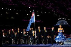 Wheelchair rugby player Greg Smith of Australia carries the flag during the Opening Ceremony of the London 2012 Paralympics at the Olympic Stadium on August 29, 2012 in London, England. Performers carried country names on umbrellas wearing cheeky flag themed dresses.