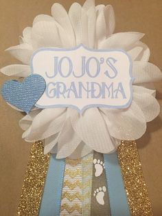 This pin is perfect for any baby shower addition! Can be pinned to any piece of clothing!  White flower pin with ribbons starting from middle: ️Gold chevron, blue sheer footprints, light blue satin, gold glitter with a tag that reads ...  Choose one: (Include choice in order please) Mommy Mommy to be Grandma Auntie *custom saying/name*  Blue tag with blue heart on tag corner. Attached to the back of ribbon is a pin to attach to clothing.  This pin/corsage measures approx. 6 inches ...