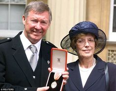 Cathy proudly stands next to Ferguson as he receives his knighthood in 1999