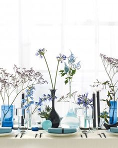 Blue & Purple Wedding Tablescape: Arrange lone stems—a mix of full plumes and reedy stalks such as caspia and agapanthus—in vessels of various heights and shapes. Keep colors consistent for maximum impact. To make a random assortment of flowers look anything but, map the vases out first. Place the tallest shapes in the center, anchor the outer edges with medium-size pieces, and fill them in with small containers. When you're done, add a stem or two to each.