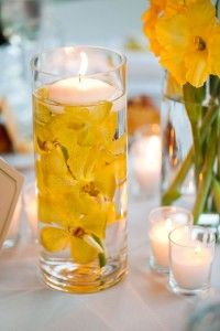 Yellow candle centerpiece with submerged yellow floral. …