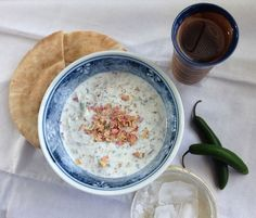 bowl of abdoogh khiar (Persian yogurt cucumber soup) with piece of bread | FigandQuince.com (Persian Cooking and Culture blog)