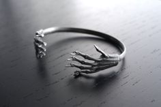 """Inspired by the three witches passage in macbeth, this bangle is made of two sterling silver casts of Mummified squirrel paws. It has been oxidised or """"Blackened"""" To make it a gorgeous dark grey colour. It is adjustable and can me made wider to slip it on and squeezed smaller when on the wrist."""