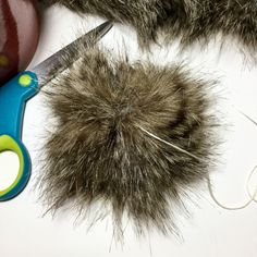 The easiest free Faux Fur PomPom Tutorial to make those super trendy fur PomPoms. Attach them to hats, scarves or bags, they sure are cute and easy to make!