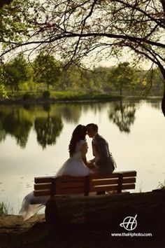 Wedding photo session with Ema and Eli at Lake Katherine Nature Center and Botanic Gardens.  Bride and groom kissing on a bench by the lake. Photo by Doru Halip for H Photography